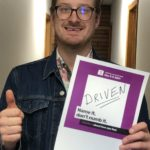 """Tristan holds up a signfrom Mental Health Week that says """"Driven"""""""